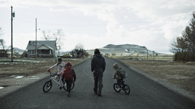 man_and_children_on_bikes_in_street